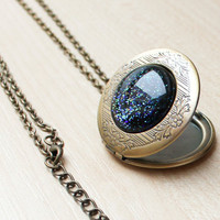 Cosmic locket pendant necklace with galaxy glitter on black background set in vintage look bronze locket
