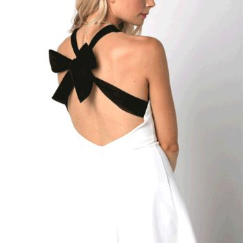 Featuring a scoop neckline, contrast criss-cross back with adjustable self-tie bow design, flare skirt, and finish with rear zipper closure. Unlined.