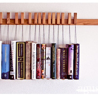 Custom made wooden book rack in Oak. The pins are also bookmarks.