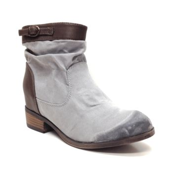 Featuring oil finish suede upper, leatherette collar with buckled strap embellishment, leatherette quarter, slouchy shaft, stitching detail, round toe, flat heel, concealed lift insole, and side zipper closure for easy on/off.