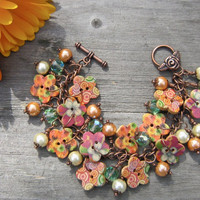Tropical floral button bracelet, tones of orange, pink and green.