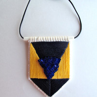 Embroidered pendant necklace collegiate geometric design yellow and blues with blue beaded accent on cream bone bead and leather cord