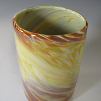Hand blown drinking glass in modeled warm earth tones.