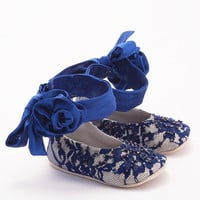Baby booties in blue rose-appliquéd silk and lace covered leather