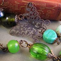 Green glass necklace with butterfly filigree charm and copper details