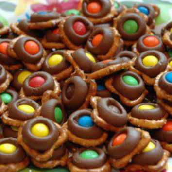 melt Hershey kisses onto tiny twist pretzels (275 degrees, 3 minutes), remove, and immediately press a single mm; on each. Refrigerate.