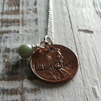Hand stamped LUCK necklace with a hand wrapped light teal bead
