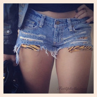 distressed, ripped shorts with tiger stipe print pockets frayed.
