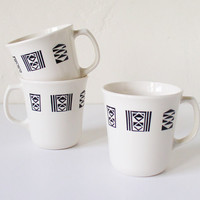Three white mugs with geometric patterns