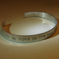 Stamped aluminum cuff bracelet with there is more to life than increasing its speed