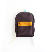 Dark brown wool backpack with mustard pouch.