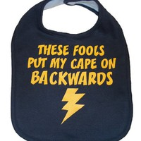 These Fools Put My Cape On Backwards Infant Toddler Superhero Bib Funny Baby Shower Gift - Navy / Yellow