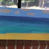 Daytime beach scene painted on pallet wood