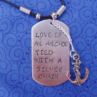 Hand stamped stainless steel necklace has the words ( love is an anchor tied with a silver chain)