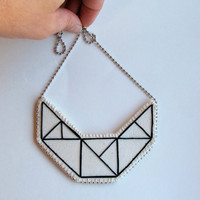 Small embroidered geometric bib necklace on cream muslin with black outline